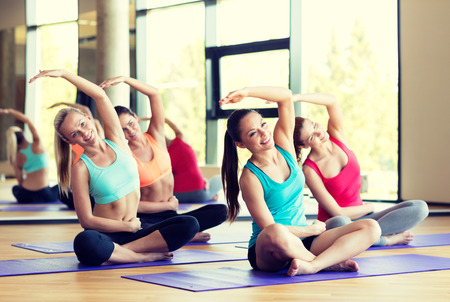 gym class: fitness, sport, training and lifestyle concept - group of smiling women stretching in gym