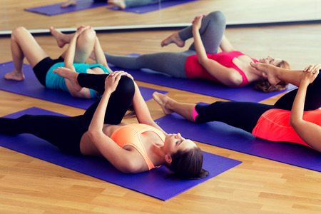 fitness, sport, training and lifestyle concept - group of women stretching in gym Фото со стока