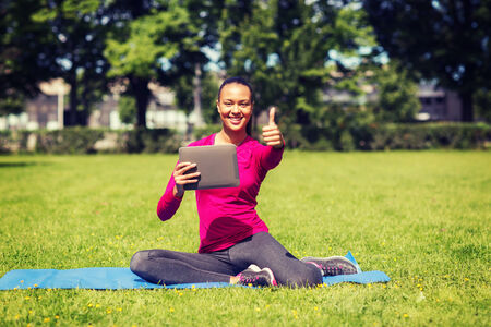 mat like: fitness, park, technology, gesture and people concept - smiling african american woman with tablet pc showing thumbs up outdoors Stock Photo