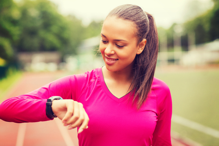 heartrate: fitness, sport, training, technology and lifestyle concept - smiling african american woman with heart-rate watch on track outdoors
