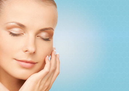 touching face: beauty, people and health concept - beautiful young woman touching her face over blue background