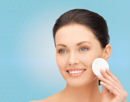 cotton pad: beauty, people and health concept - beautiful smiling woman cleaning face skin with cotton pad over blue background Stock Photo