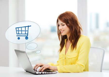 people, leisure and technology concept - smiling young woman with laptop computer and trolley icon shopping online at home photo