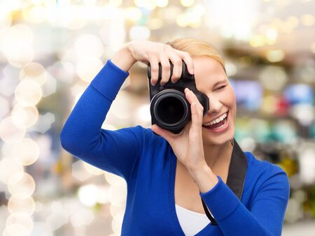 photography, technology, holidays, and people concept - smiling young woman taking picture with digital camera over lights background photo