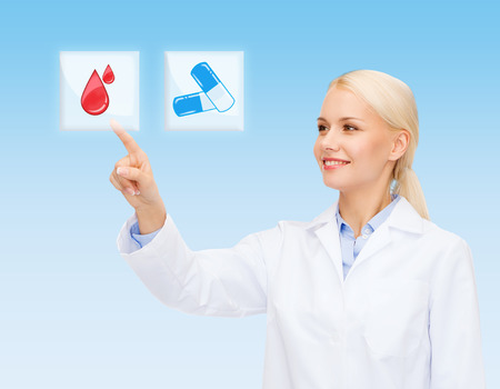 healthcare, medicine, people and technology concept - smiling young doctor or nurse pointing to icon or pressing button with pills and blood images over blue background photo