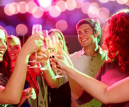 partij, vakantie, viering, het nachtleven en de mensen concept - lachende vrienden rammelende glazen champagne in club Stockfoto