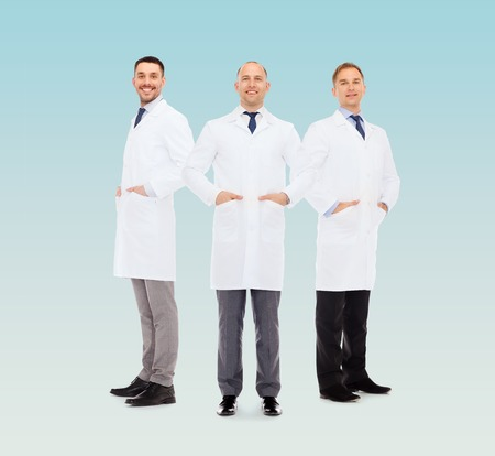 white coats: healthcare, profession and medicine concept - smiling male doctors in white coats over blue background