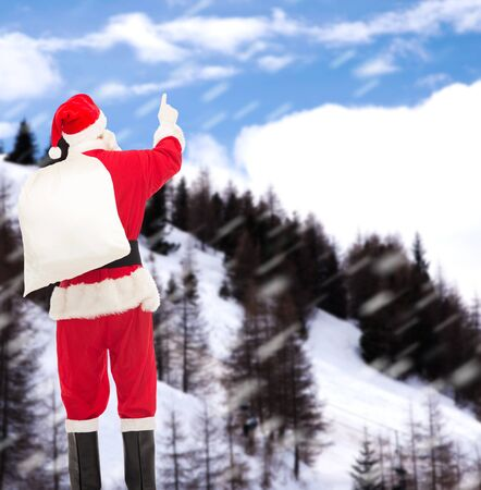 christmas, holidays and people concept - man in costume of santa claus with bag pointing finger from back over snowy mountains background photo