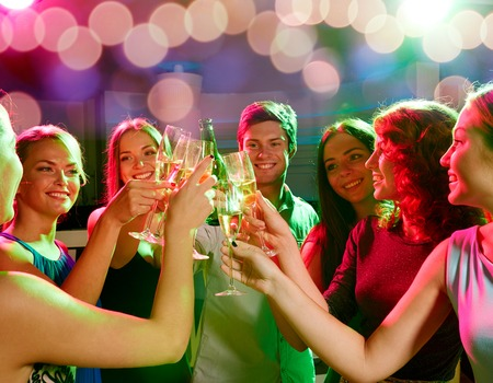 party, holidays, celebration, nightlife and people concept - smiling friends clinking glasses of champagne and beer in club Фото со стока