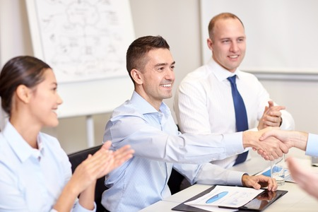teamwork: business, people and partnership concept - smiling business team shaking hands and applauding in office