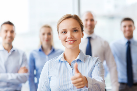 thumbs up group: business, people, gesture and teamwork concept - smiling businesswoman showing thumbs up with group of businesspeople in office
