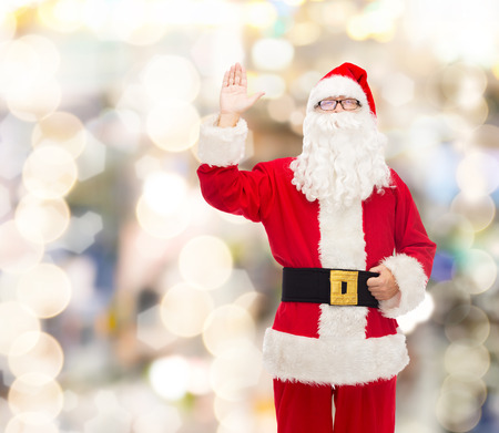 st nick: christmas, holidays, gesture and people concept - man in costume of santa claus waving hand over lights background