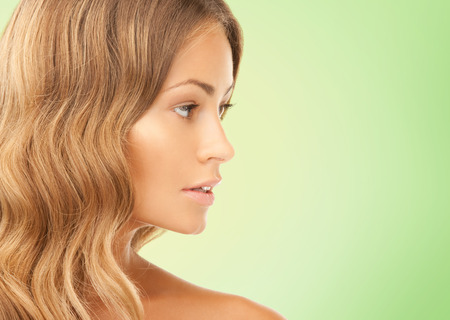 long nose: beauty, people and health concept - beautiful young woman face over green background Stock Photo