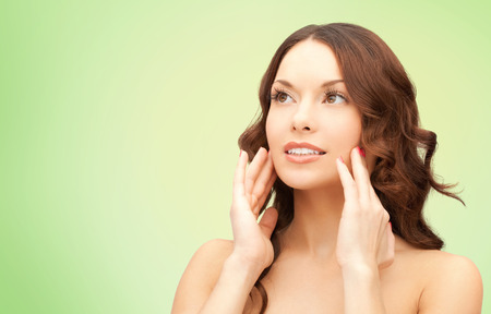 smooth skin: beauty, people and health concept - beautiful young woman touching her face over green background