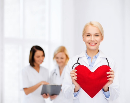 heart doctor: healthcare and medicine concept - smiling female doctor with heart and stethoscope