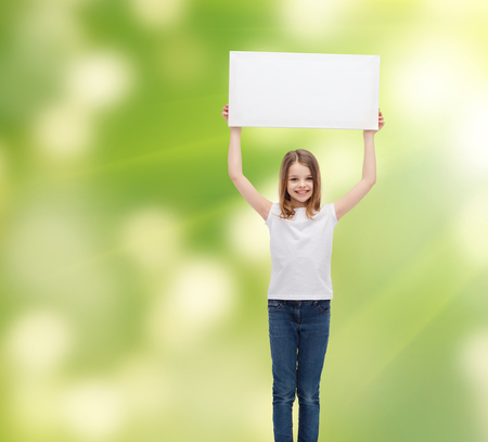 cute teen girl: advertisement, childhood, happiness and people concept - smiling little child in white t-shirt holding blank board over green background