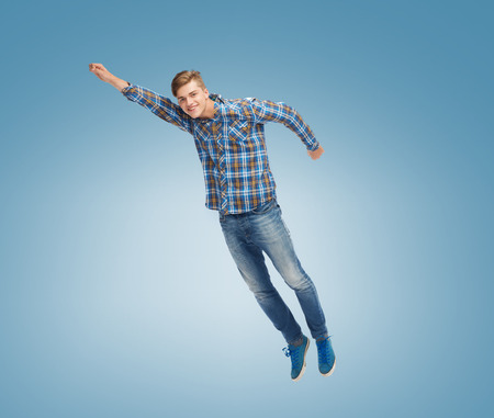 flying man: happiness, freedom, movement and people concept - smiling young man flying in air over blue background Stock Photo