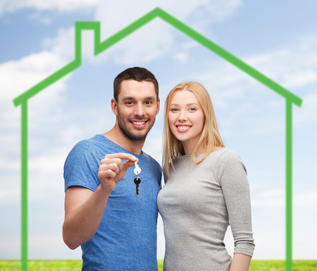 love, home, people and family concept - smiling couple holding house key over green house and blue sky with grass background photo