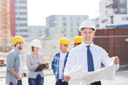 ビジネス、建物、チームワークおよび人々 のコンセプト - クリップボードと屋外の青写真と hardhats で笑顔の建築者のグループ