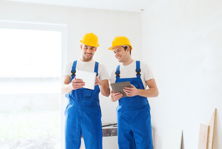 computer applications: building, renovation, technology, electricity and people concept - two builders with tablet pc computers indoors Stock Photo