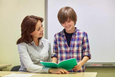junior student: education, elementary school, learning, examination and people concept - school boy with notebook and teacher in classroom