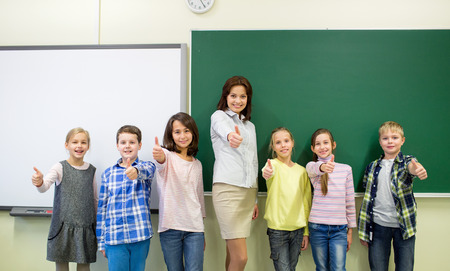primary education: education, elementary, gesture and people concept - group of school kids and teacher showing thumbs up in classroom