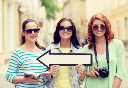 directive: tourism, travel, vacation, direction and friendship concept - smiling teenage girls with white arrow showing direction outdoors Stock Photo