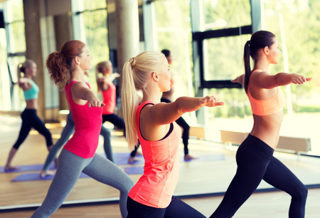 aerobics: fitness, sport, training and lifestyle concept - group of smiling women stretching in gym
