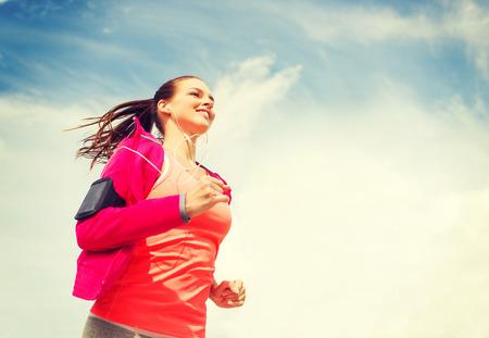 フィットネス、スポーツ、ライフ スタイルのコンセプト - 屋外を実行するイヤホンで若い女性を笑顔 写真素材
