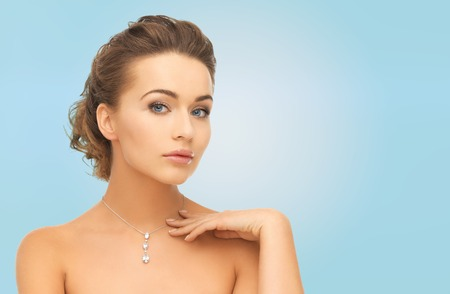 beauty, people and jewelry concept - woman wearing shiny diamond pendant over blue background Stock Photo
