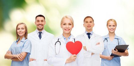 medicine, profession, teamwork and healthcare concept - group of smiling medics or doctors holding red paper heart shape, clipboard and stethoscopes over green background