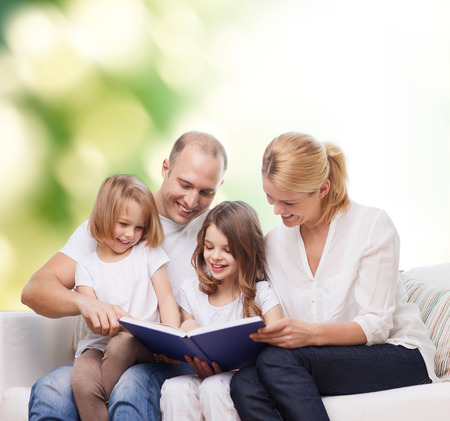family, childhood, ecology and people - smiling mother, father and little girls reading book over green background photo