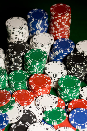 table surface: gambling, fortune, game and entertainment concept - close up of casino chips on green table surface Stock Photo