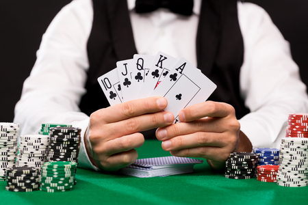 croupier: casino, gambling, poker, people and entertainment concept - close up of poker player with playing cards and chips at green casino table