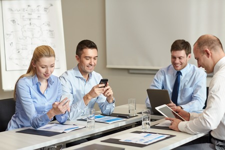 businessman phone: business, people and technology concept - smiling business team with smartphone and papers meeting in office Stock Photo