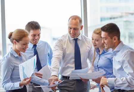 business, teamwork, people and technology concept - smiling business team with papers meeting and talking in office Stock Photo - 35172767