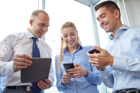 man on cell phone: business, teamwork, people and technology concept - business team with tablet pc and smartphones meeting in office
