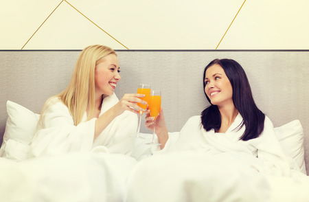 hotel, travel, friendship and happiness concept - smiling girlfriends having breakfast in bed photo