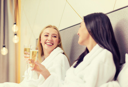 woman resting: hotel, travel, friendship and happiness concept - smiling girlfriends with champagne glasses in bed