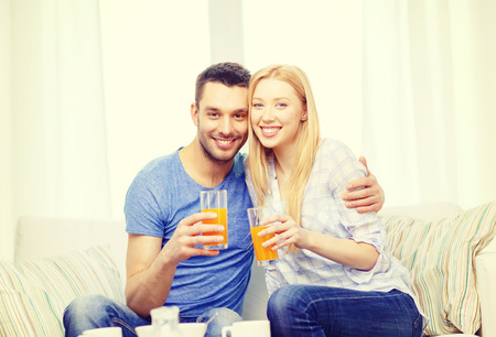 citrus family: love, family, healthy food and happiness concept - smiling happy couple drinking juice at home