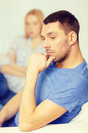 love, family and happiness concept - upset young man with man on the back at home photo