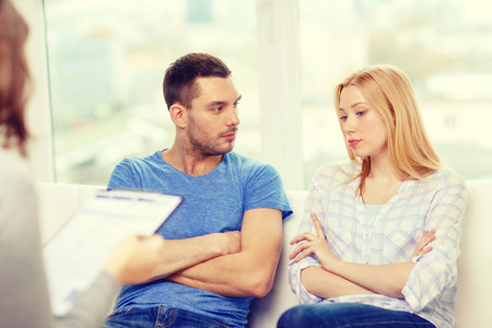 husbands and wives: love, family, phychology and relationship problems concept - young couple with a problem at psychologist office Stock Photo