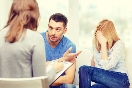 two men talking: love, family, phychology and relationship problems concept - young couple with a problem at psychologist office Stock Photo