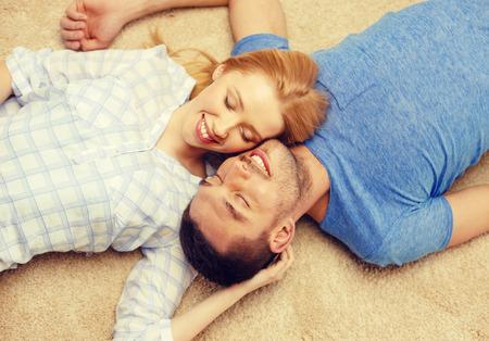 pareja en casa: el amor, la familia y la felicidad concepto - sonriente pareja feliz acostado en el piso en casa