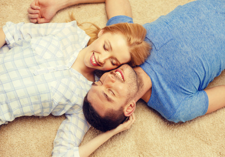 2 people at home: love, family and happiness concept - smiling happy couple lying on floor at home