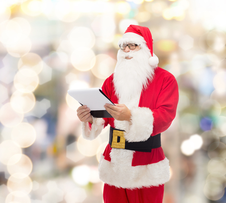 st nick: christmas, holidays and people concept - man in costume of santa claus with notepad over lights background