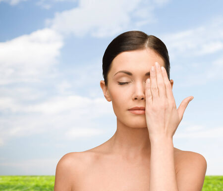 bare women: beauty, people and health concept - smiling young woman covering half of face with hand over blue sky and grass background