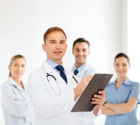 medics: medicine, profession, teamwork and healthcare concept - smiling male doctor with clipboard and stethoscope writing prescription over group of medics