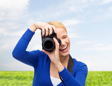 photography, technology, summer and people concept - smiling young woman taking picture with digital camera over blue sky and grass background photo