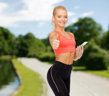 sport, fitness, technology, internet and healthcare concept - smiling sporty woman with smartphone showing thumbs up